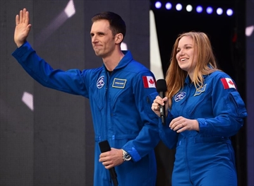 Canada's newest astronauts Joshua Kutryk and Jennifer Sidey acknowledge the crowd during Canada 150 celebrations on Parliament Hill in Ottawa on Saturday, July 1, 2017. THE CANADIAN PRESS/ Sean Kilpatrick