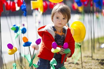 Marlowe Barrett, 20 months, wades through a meadow of more than 1,000  plastic flowers outside Christ Church Deer Park April 20, 'planted' as part of the church's Easter celebrations.