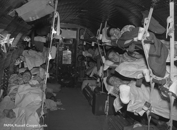 Wounded Canadian soldiers return from the Korean War, in cots on a plane, Malton Airport, July 23, 1951.