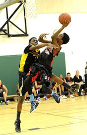 Tigers #20 Kharmon Blake forces his way to the basket, past Eagles defender # 7 Elisha Ampofo.