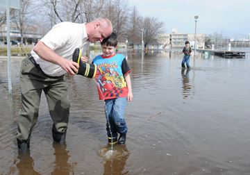 Derek Green helps his sock-soaked son Samuel, 7, get water out of his boot at Del Crary Park on Monday (April 21).Lance Anderson | This Week