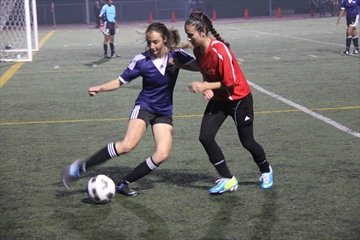 The St. Marcellinus Spirit hosted their fifth annual Friday Night Lights soccer triple header last night. Chanel Vani of the Cardinal Leger Lancers (left) tries to clear the ball with the Spirit's Ariana Mouratidis closing in.