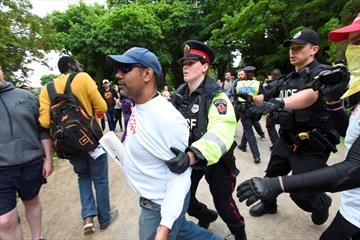 Police escort a protester away from Hamilton Pride festivities Saturday.