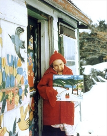 Maud Lewis stands outside her humble, yet colorful home. Lewis, who died in 1970, holds one of her paintings.