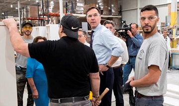 Finance Minister Bill Morneau chats with workers at a kitchen counter factory, in Montreal on Tuesday, October 17, 2017. THE CANADIAN PRESS/Paul Chiasson
