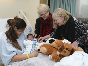 Metroland Media Toronto's Colleen LeBlanc, right, and Cathie Orban bring Nicholas Josiah and his mother Brizia Sequeira some holiday cheer at the Scarborough Hospital-Birchmount campus.