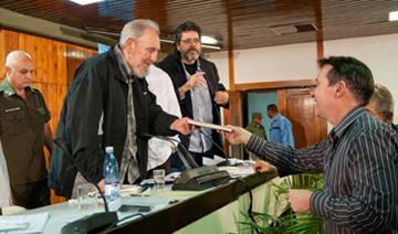 Presenting book to Fidel Castro