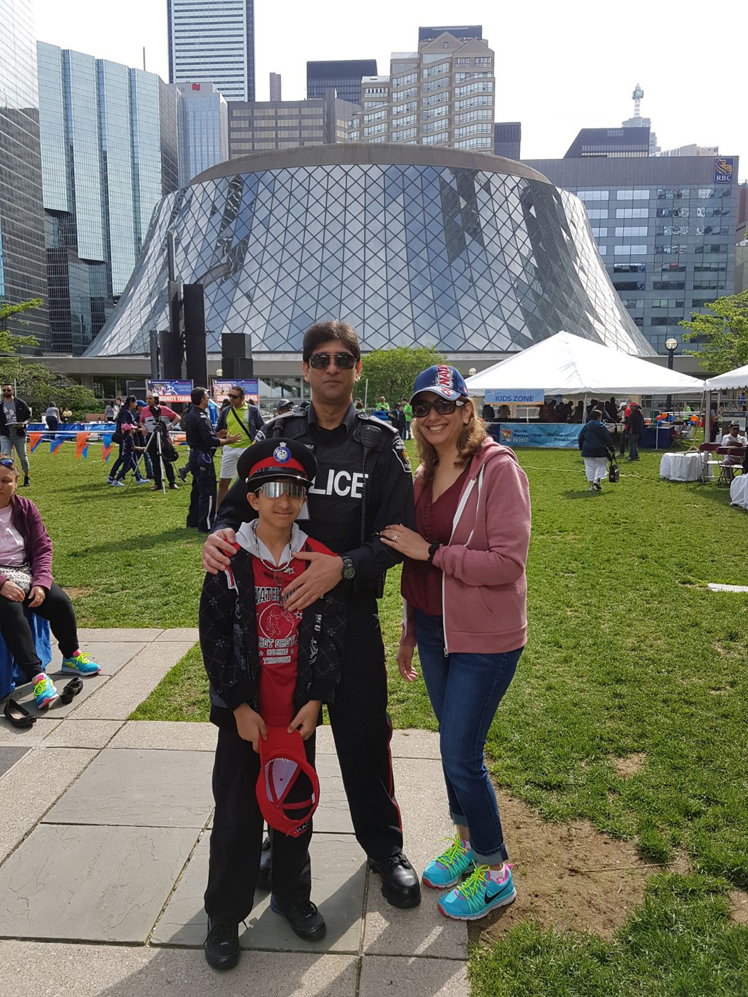 A woman, a man and a boy stand in front of Roy Thomson Hall in Toronto