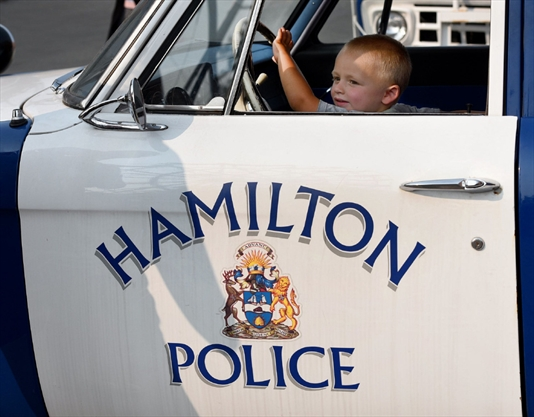 Grayson Thombs, 3, checks out the view behind the wheel of an antique Hamilton police car on display.