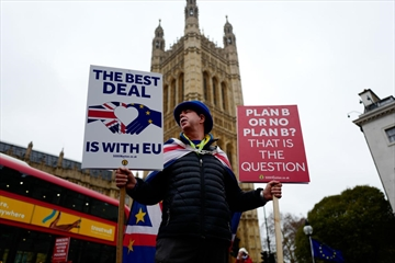 Anti-Brexit activist Steve Bray stands holding placards outside the Houses of Parliament in central London on January 16, 2019. Amid a crumbling Parliament, Britain's Brexit factions are still deadlocked, with competing plans and no clear majority for any of them.