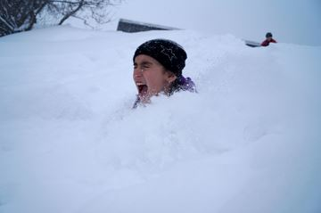 Shannon Jalbert, 9, ends up neck deep in snow after sledding at the toboggan hill behind the Burk's Falls Arena.