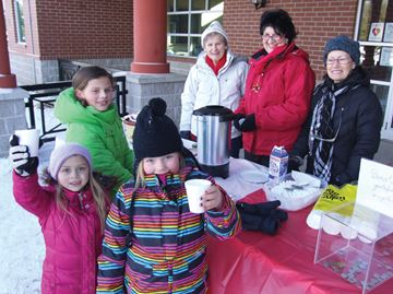 Sisters Abby and Grace Riha, along with friend Meaghan Braun, enjoyed the hot chocolate served up by Friends of the Innisfil Public Library members Sheila Hall, Ona Kane and Marie McArthur.