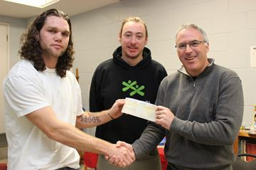 (Left to Right) Inmate Jarrod Shook presents a cheque for $1,100 to Jeff Helsby and Tony Gargaro of the Boys and Girls Club of Kingston and Area