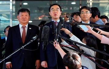 FILE - In this June 1, 2018, file photo, South Korean Unification Minister Cho Myoung-gyon, center, speaks to the media before leaving for the border village of Panmunjom to attend South and North Korean meeting, at the Office of the South Korea-North Korea Dialogue in Seoul, South Korea. Seoul said the rival Koreas agreed on high-level talks next Monday, Aug. 13, 2018, to prepare for a leaders' summit. The announcement Thursday, Aug. 9, 2018, by an official at the South's Unification Ministry comes amid attempts by Washington and Pyongyang to follow through on nuclear disarmament vows made at a summit in June between President Donald Trump and leader Kim Jong Un. (AP Photo/Ahn Young-joon, File)