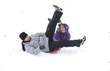 Here, mom Luisa Bonura and daughter Vanessa ,9, enjoy the thrills and spills  of the deep powder snow,while sledding in the parkette near Headon Road and Upper Middle.