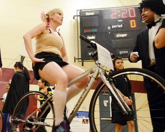 Science teacher Albert Nazareth looks on as math teacher Erinn Cooney  rides.