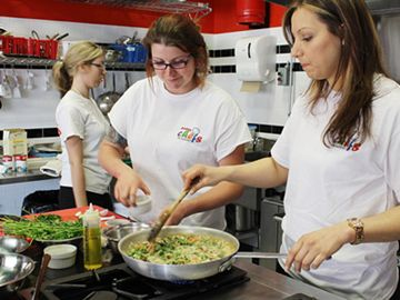 Laura Watt and Sabrina Cellupica make pasta primavera at the Petits Chefs Academy kitchen May 17 as part of Jamie Oliver's Food Revolution Day.