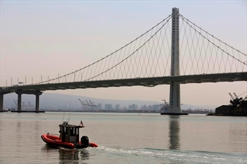 A dull haze fills the air around the San Francisco Bay Bridge and Oakland, Calif., Wednesday, Aug. 8, 2018. Blazes in Northern California and near Yosemite National Park have caused air quality to worsen in cities miles away. (AP Photo/Lorin Eleni Gill)