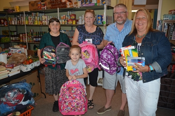 Village of Hope is preparing to distribute backpacks and school supplies to families ahead of the return to school. Pictured are, from left, Anna and Aggie Bueckert, Julie Roddy, Dave Robitaille of IBM Canada and Village of Hope director Cheryl Keddy-Scott.