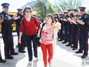 York Regional Police officers form a guard of honour for Hanah Catalano, 12, from Stouffville's St. Mark Catholic Elementary School. Hanah was the Special Olympic torch bearer and was accompanied May 16 by education assistant Margaret Grandison during a ceremony at Unionville's Bill Brothers Secondary School.