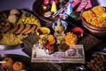 Diya with crackers, sweet or mithai, dry fruits, indian currency notes, marigold flower and statue of Goddess Laxmi