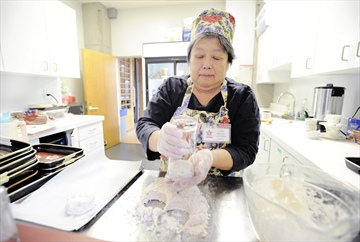 Volunteer Linda Oikawa makes cheese onion biscuits at the Momiji Cafe.