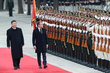 Chinese President Xi Jinping, left, accompanies French President Emmanuel Macron to view an honour guard during a welcoming ceremony outside the Great Hall of the People on Wednesday in Beijing. Macron's state visit suggests the United States risks being sidelined on the global stage under President Donald Trump.