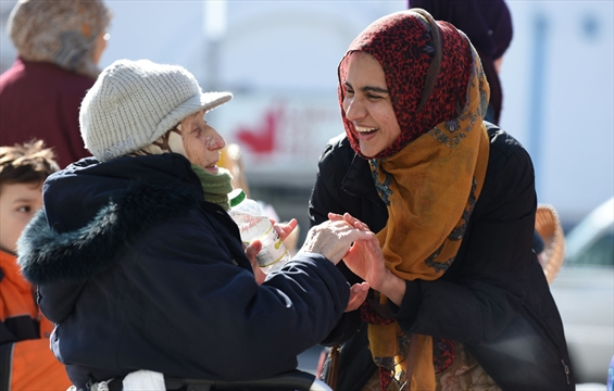 Muslim women give out treats and greetings to disp…