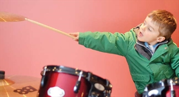 Evan Lalonde, 3, tries out the drum set at the grand opening of the Orléans School of Rock on March 29. The music school is located on St. Joseph Boulevard. Students will present community performances, performing in groups as rock bands.