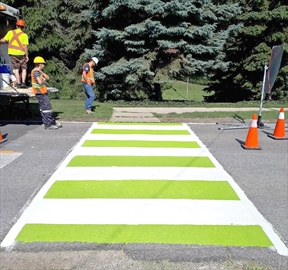 Staff with the town of Lincoln install new painted crosswalks at a busy intersection. The colourful crosswalks are meant to grab the attention of motorists.