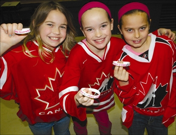 Havelock Belmont Public School Grade 4 students Kadence, Sarah and Bri show of their Pink Day bracelets while wearing Team Canada red and white during the school's bullying awareness activities at the school which focussed on working together as a team.