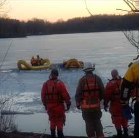 Rescue workers attempt to find a man who fell into the ice in a Waterford North conservation area pond Saturday evening.