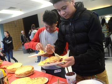 Aldwin Palmieri and Brandon Corpuz load up their Blinchiki in the Russian booth during Taste of Joan at St. Joan of Arc  Catholic High School in Vaughan, Thursday.