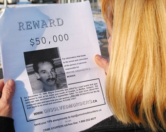 Diane Greavette holds a poster with details about her husband Wayne's murder.