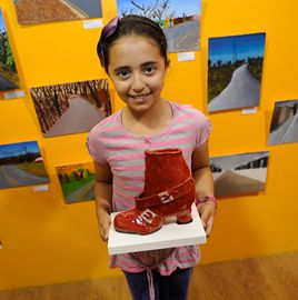 Emily Rodriguez, ten, displays a clay boot she made.