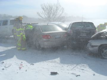 PORT PERRY -- Scugog firefighters and Durham paramedics work to remove a motorist from one of the 30 or so vehicles that were involved in a pile-up on Thursday morning on the Hwy. 7A causeway just east of Port Perry. February 27, 2014