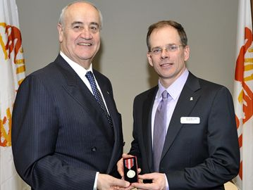 Federal minister Julian Fantino (left) presents Clearview native Kevin McCort with the Queen Elizabeth II Diamond Jubilee Medal for his work with CARE Canada.