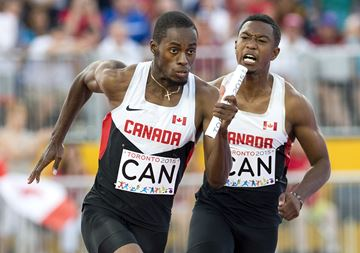 Dontae passes the baton to team mate Brendon Rodney during the 4x100m relay semi-finals.