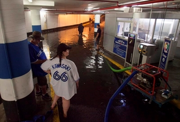 Toronto Blue Jays fans get stuck in the Rogers Centre as the entrance to the parking garage floods with torrential rain, in Toronto on Tuesday, August 7, 2018. THE CANADIAN PRESS/Fred Thornhill