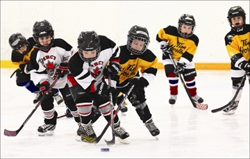 Percy Bulldog players, Taylor Moore and Nathan Harwood (second and third in from the left) scramble to keep control of the puck in the final game of the IP-Tyke Tournament played against the Cobourg team. The day-long tournament was hosted by Percy Minor Hockey.