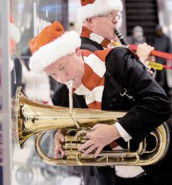 Dan Douglas plays his French horn against a storefront window during Santa's arrival parade at the Scarborough Town Centre.