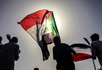 Sudanese demonstrators march with national flags as they gather during a rally demanding a civilian body to lead the transition to democracy, outside the army headquarters in the Sudanese capital Khartoum on Saturday, April 13, 2019.