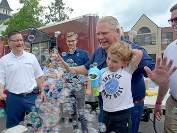 Premier Doug Ford and five-year-old Rowan Wallington of Fonthill shoot some bubbles on Pelham Street during Summerfest in Pelham on Saturday. Ford was invited to the annual summer celebration by Niagara West MPP Sam Oosterhoff.