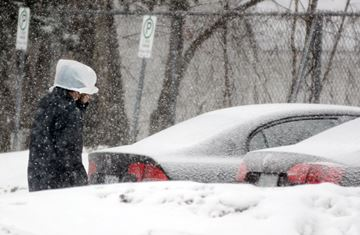 A pedestrian wears a plastic bag on his head to protect against the snow.