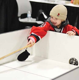 Barrhaven's Tyler Finn, 2, is all smiles as he plays mini sticks with his big brother at Hockeyfest on Nov. 24 at the Ernst and Young Centre. The two-day event was held for the first time this year and featured games, vendors and speakers.