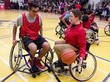 Rick Hansen SS Grade 11 student Ibrahim Dandach tries out wheelchair basketball with the help of Paralympian Tamara Steeves from Mississauga in a demonstration of wheelchair basketball at Rick Hansen SS on Friday February 28.