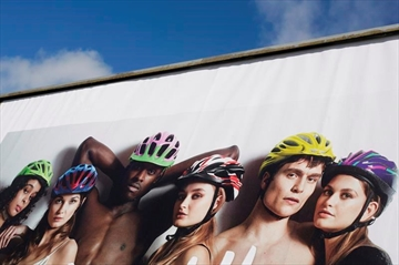 A poster of a bike helmet campaign is displayed in front of Germany's transport ministry in Berlin, Monday, March 25, 2019. The cycling safety campaign has drawn accusations of sexism even inside the governing coalition for featuring scantily clad women. (AP Photo/Markus Schreiber)