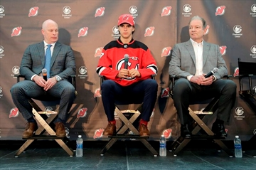 New Jersey Devils' Nico Hischier, center, sits with head coach John Hynes, left, and general manager Ray Shero during a news conference in Newark, N.J., Monday, June 26, 2017. The 18-year-old center was the first Swiss-born player to be drafted first overall in the NHL draft. (AP Photo/Seth Wenig)