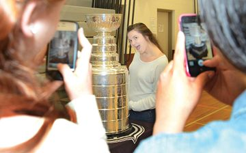 SDSS senior girls basketball  player Taylor Oake poses with the Stanley Cup while teammates photograph her durinig a visit to the school.