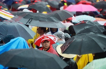 People use umbrellas to shelter themselves from the rain during Canada 150 celebrations in Ottawa on Saturday, July 1, 2017. THE CANADIAN PRESS/Justin Tang